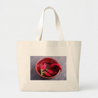 Hot red chili peppers on a fabric background large tote bag