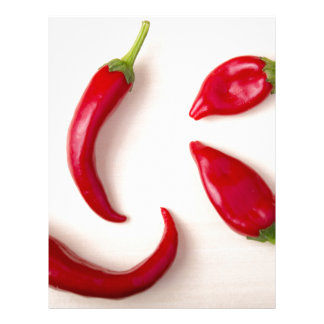 Hot red chili peppers on a light wooden board letterhead