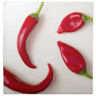 Hot red chili peppers on a light wooden board napkin