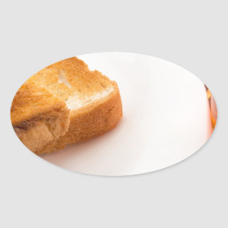 Hot toast with butter and cup of tea oval sticker