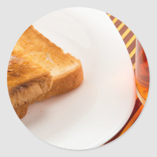 Hot toast with butter and cup of tea round sticker
