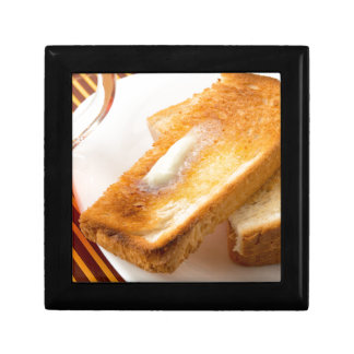 Hot toast with butter on a white plate close-up gift box