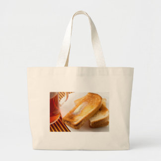 Hot toast with butter on a white plate close-up large tote bag