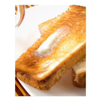 Hot toast with butter on a white plate close-up letterhead