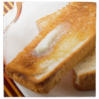 Hot toast with butter on a white plate close-up napkin