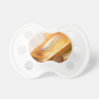 Hot toast with butter on a white plate close-up pacifier