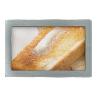 Hot toast with butter on a white plate close-up rectangular belt buckle