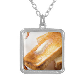 Hot toast with butter on a white plate close-up silver plated necklace