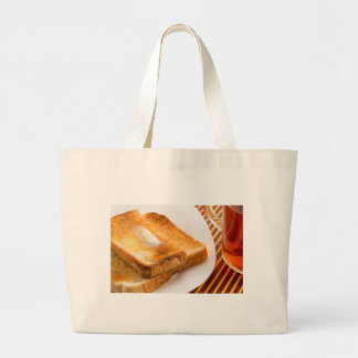 Hot toast with butter on a white plate large tote bag