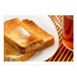 Hot toast with butter on a white plate postcard