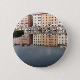 Houses and boats are reflected in the water 2 inch round button