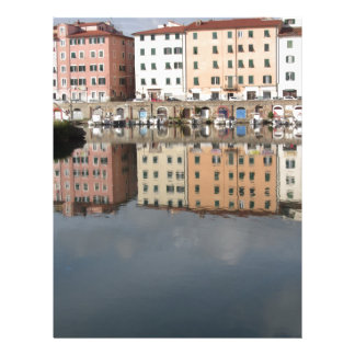 Houses and boats are reflected in the water letterhead