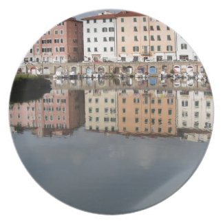 Houses and boats are reflected in the water plate