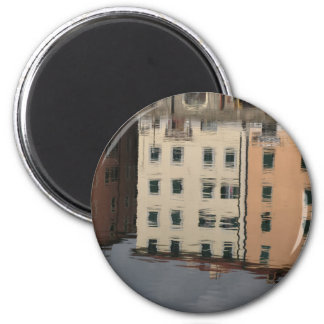 Houses are reflected in the tranquil water 2 inch round magnet