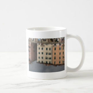 Houses are reflected in the tranquil water coffee mug