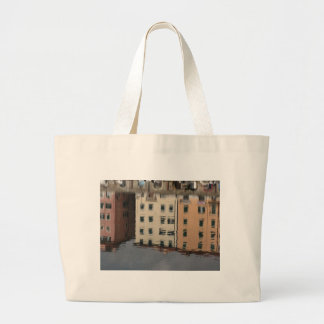 Houses are reflected in the tranquil water large tote bag