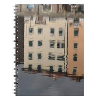 Houses are reflected in the tranquil water notebook
