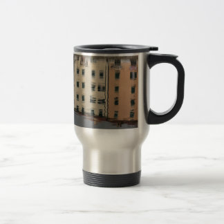 Houses are reflected in the tranquil water travel mug