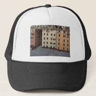 Houses are reflected in the tranquil water trucker hat