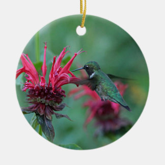 Hummingbird feeding on pink flowers round ceramic ornament