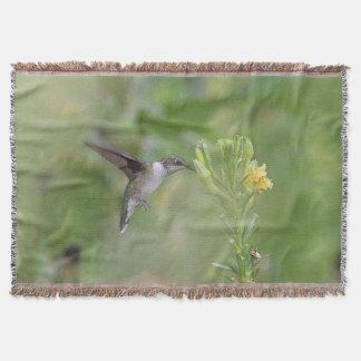 Hummingbird feeding on yellow flowers throw
