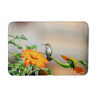 Hummingbird on a flowering plant bath mat