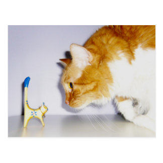 Humorous Cat Staring at Wooden Kitty Statue Postcard
