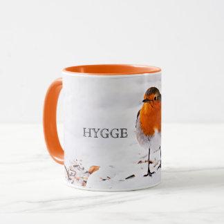 Hygge with a cute robin bird in snow mug