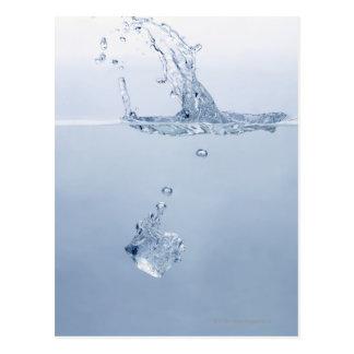 Ice cube splashing into water postcard