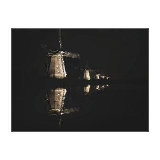 Illuminated windmills at night canvas print