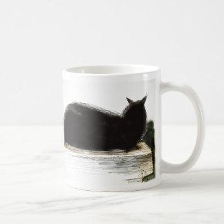 Inky black cat rests on ledge coffee mug