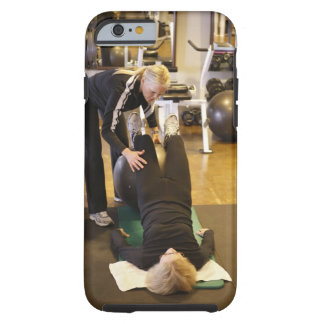 Instructor helps senior client with stretches tough iPhone 6 case