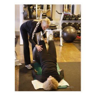 Instructor helps senior client with stretches postcard