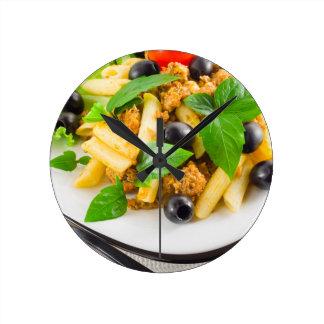 Italian pasta rigatoni with bolognese, beef round clock