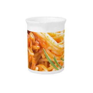 Italian spaghetti with vegetable sauce closeup pitcher