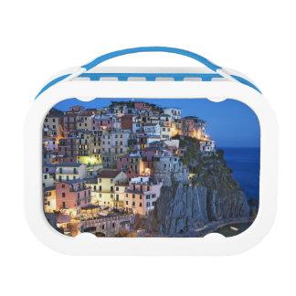 Italy, Manarola. Dusk falls on a hillside town Lunch Boxes