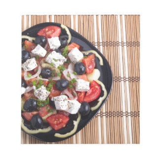 ITop view of a Greek salad with fresh vegetables Notepad