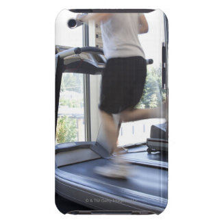 Jeune homme courant sur un tapis roulant au club coque iPod touch