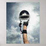 Joueur de football tenant le casque en air affiche