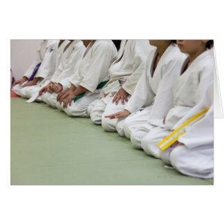 Judo player of the child sits down to one line card