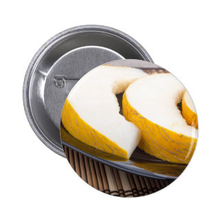 Juicy yellow melon on wooden background 2 inch round button