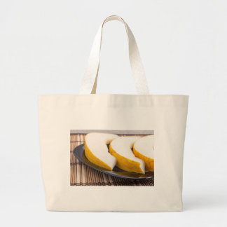 Juicy yellow melon on wooden background large tote bag