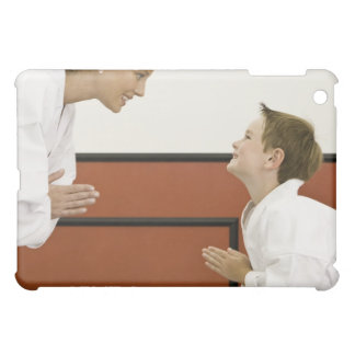 Karate teacher and boy (4-5 years) bowing to cover for the iPad mini