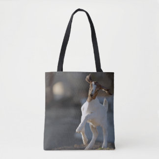 Kid goat playing in ground. tote bag