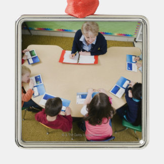 Kindergarten students sitting at table with metal ornament