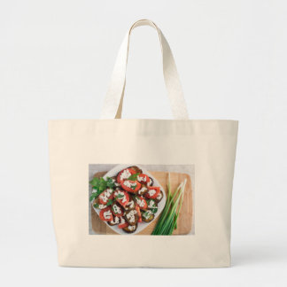 Kitchen table with a dish of stewed eggplant large tote bag