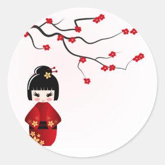 Kokeshi doll under sakura branch round sticker