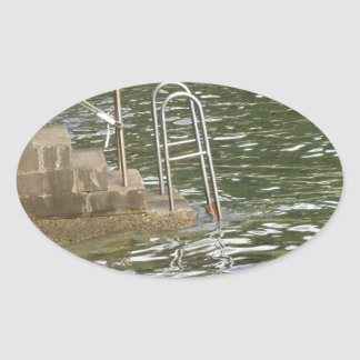 Ladder descending into the sea water oval sticker