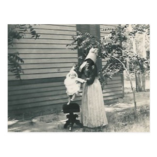 lady with bonnet putting child on seat post card