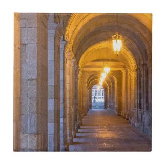 Lamp lit stone hallway, spain ceramic tiles